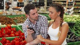 Kontrollerande lista för älskvärda par på deras smarta telefon, medan shoppa för mat lager videofilmer