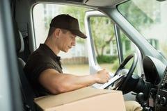 Kontrollerande lista för leveransman i skåpbil fotografering för bildbyråer