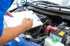 Kontrollerar den hållande skrivplattan för mekanikermannen och bilen arkivfoton