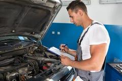 Kontrollerar den hållande skrivplattan för mekanikermannen och bilen royaltyfri foto