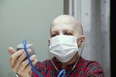 Kontrollerar den skalliga kvinnan för tålmodig bröstcancer ditt blodtryck i en steril maskering Arkivfoton