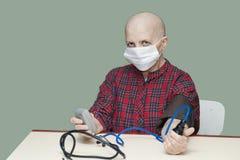 Kontrollerar den skalliga kvinnan för tålmodig bröstcancer ditt blodtryck i en steril maskering Royaltyfri Foto