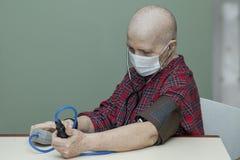 Kontrollerar den skalliga kvinnan för tålmodig bröstcancer ditt blodtryck i en steril maskering Royaltyfri Fotografi