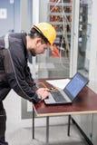 Kontrollerar den tjänste- teknikern för fältet reläskyddssystemet med lapt royaltyfri bild