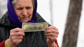 Kontrollerar hållande pengar för den gamla kvinnan i hennes händer äkthet Äldre kvinna som kontrollerar dollarpengar stock video