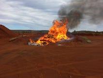 Kontrollierter Feuerbrand im Abfalltipp mit schwarzem Rauche und Flammen Stockfotografie