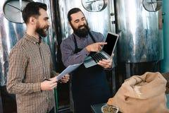 Kontrollkvalitet för två uppsökt män av malten Arbetare av analys för bryggeriuppförandeprodukt arkivfoton