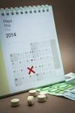 Kontrollpreventivpillerar på en kalender Arkivbild