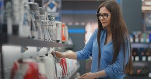 Kontuar elektronika sklep Młoda piękna brunetki kobieta trzyma elektrycznego czajnika w jej rękach, studiuje cenę zbiory