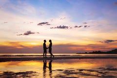 Kontur av afectionatepar på stranden på solnedgången Fotografering för Bildbyråer