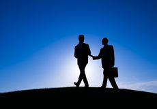 Kontur av affärsfolk som möter på kullen Arkivbild