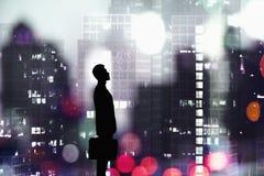 Kontur av affärsmannen som rymmer en portfölj med en stad på nattetid i bakgrunden royaltyfria bilder