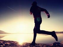 Kontur av aktiv idrottsman nenlöparespring på soluppgångkust Sund livsstilövning för morgon royaltyfri foto