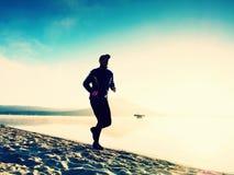 Kontur av aktiv manspring för sport på sjöstranden på soluppgång Sund livsstil royaltyfria foton