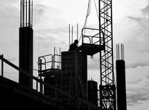 Kontur av arbetare mellan konkreta pelare med armaturer på konstruktionsplatsen, b&w royaltyfri fotografi