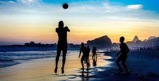 Kontur av banhoppningmannen som spelar strandfotboll på bakgrunden av den härliga solnedgången på den Copacabana stranden, Rio de arkivbilder