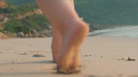 Kontur av barns fot som g?r p? v?t sand in l?ngs en tropisk strand p? en tropisk havbakgrund Begrepp arkivfilmer