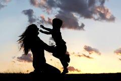 Kontur av barnspring som kramar modern på solnedgången Arkivbild
