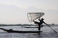 Kontur av bergskedja och den traditionella burmese fiskaren som balanserar på hans fartyg i gryningen på Inle sjön, Myanmar royaltyfri bild