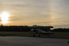 Kontur av biplanen omkring som ska tas av under solnedgång Arkivfoto