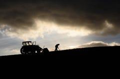 Kontur av bonden med traktoren som arbetar och gräver högt upp i molnen Arkivfoto