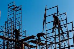 Kontur av byggnadsarbetare mot himmel på material till byggnadsställningwi Royaltyfria Bilder