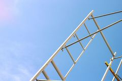 Kontur av byggnadsarbetare på ställningarbete under en blå himmel fotografering för bildbyråer