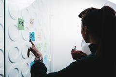Kontur av coworking folk som diskuterar idéer, medan samarbeta på projektet som delar idérikt lösningsanseende bak wal exponering arkivbilder