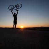 Kontur av cyklisten i solnedgång Arkivfoto