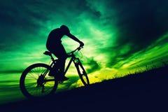 Kontur av cyklisten mot färgrik himmel på solnedgången royaltyfria bilder