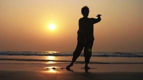 Kontur av den aktiva höga kvinnan som öva tai-chien som är gymnastisk på den sandiga stranden stock video