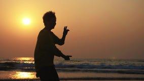 Kontur av den aktiva höga kvinnan som öva tai-chien som är gymnastisk på den sandiga stranden lager videofilmer