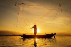 Kontur av den asiatiska fiskaren på träfartyget, fiskare i handling som kastar ett netto för att fånga sötvattensfisken i naturfl arkivfoto