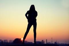 Kontur av den förföriska kvinnan på tak på den stads- solnedgången Arkivbild