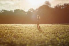 Kontur av den fria unga kvinnan på soluppgångskogbakgrund Fotografering för Bildbyråer