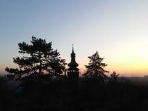 Kontur av den gamla träkyrkan med trädet på solnedgång Royaltyfri Fotografi