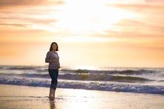Kontur av den härliga gravida kvinnan på stranden på solnedgången Royaltyfri Bild