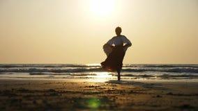 Kontur av den härliga kvinnliga ängeln som barfota går in mot havet på solnedgången arkivfilmer