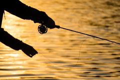 Kontur av den klipska fiskaren på solnedgången arkivbilder