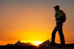 Kontur av den kvinnliga fotvandraren på solnedgången. Arkivfoto