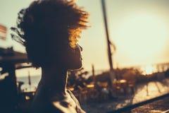 Kontur av den lockiga brasilianska flickan på solnedgång Arkivfoto