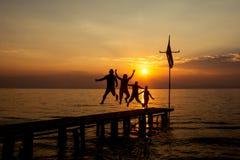 Kontur av den lyckliga aktiva familjen som hoppar på sommarsolnedgång fotografering för bildbyråer