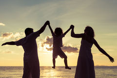 Kontur av den lyckliga familjen som som spelar på stranden på sunsen Royaltyfria Foton