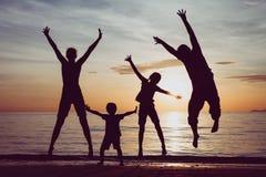 Kontur av den lyckliga familjen som som spelar på stranden på sunsen Arkivfoto