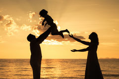 Kontur av den lyckliga familjen som som spelar på stranden på sunsen Arkivfoton