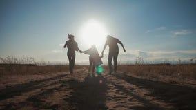 Kontur av den lyckliga familjen som som spelar med bollen på äng på solnedgångtiden Begrepp av den v?nliga familjen lager videofilmer
