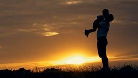Kontur av den lyckliga familjfadern av modern och två söner som utomhus spelar i fält på solnedgången
