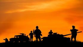 Kontur av den militära soldaten eller tjänstemannen med vapen på solnedgången Royaltyfri Bild