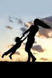 Kontur av den modersnurret och dansen med barnet på solnedgången Royaltyfria Bilder