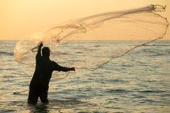 Kontur av den oidentifierade indiska fiskaren som netto kastar i havet royaltyfri bild